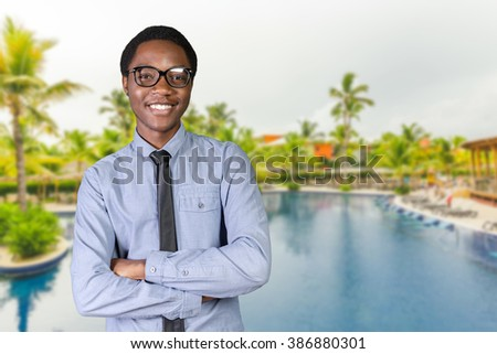 Portrait of happy young african guy with his arms crossed