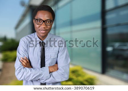 Portrait of happy young african guy with his arms crossed - stock photo