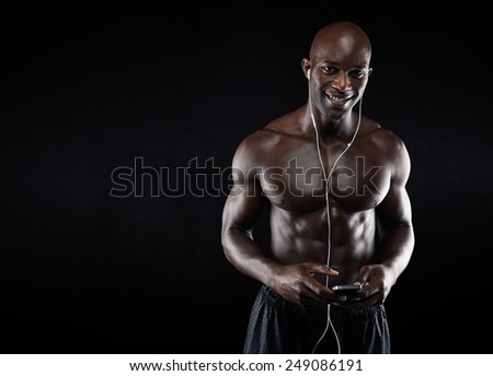 Portrait of happy young african man wearing earphones listening to music on his mobile phone. Muscular young man looking at camera smiling while listening to music on black background with copy space, - stock photo