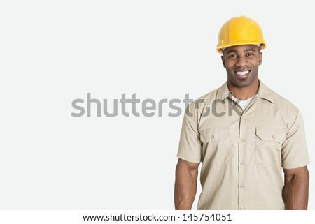 Portrait of happy young African man wearing yellow hard hat helmet over gray background - stock photo
