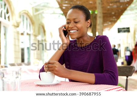 Portrait of happy young african woman at coffee shop talking on mobile phone  - stock photo