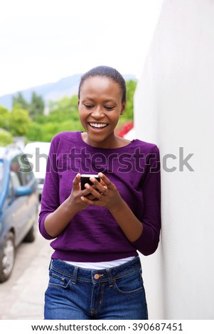 Portrait of happy young african woman leaning against wall looking at cell phone