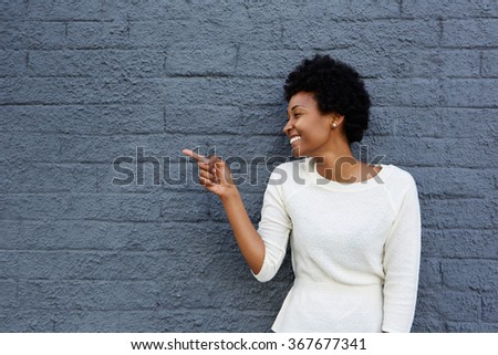 Portrait of happy young african woman pointing at copy space on gray wall  - stock photo