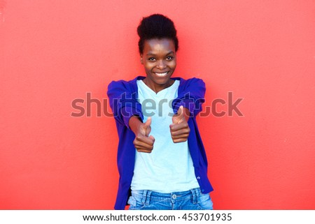 Portrait of happy young afro american woman gesturing thumbs up against red background - stock photo