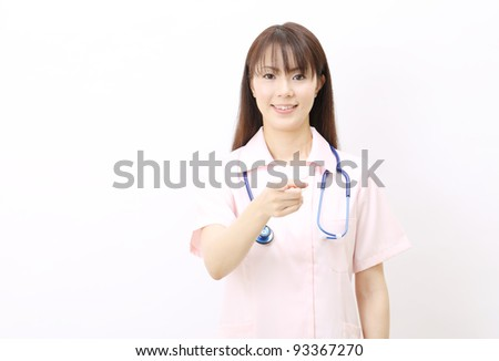 Portrait of happy young asian female nurse pointing