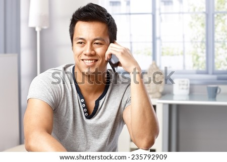 Portrait of happy young Asian man talking on mobilephone at home, smiling, looking away. - stock photo