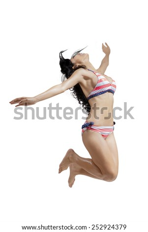 Portrait of happy young asian model jumping in the studio while wearing sexy bikini - stock photo