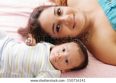 Portrait of happy young attractive hispanic mother lying with her baby on the bed - stock photo