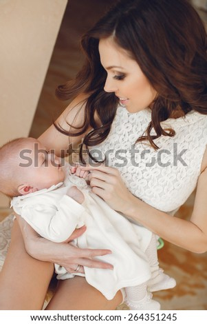 Portrait of happy young attractive mother holding in arms her little adorable baby girl.  Home cozy portrait