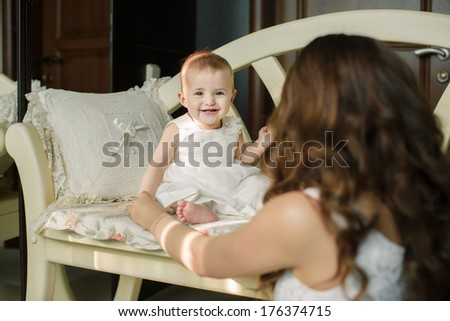 Portrait of happy young attractive mother playing with her baby girl near window in interior at haome. Pink dresses on mother and daughter