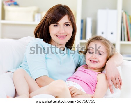 Portrait of happy young beautiful woman with little pretty daughter relaxing on a sofa at home - stock photo