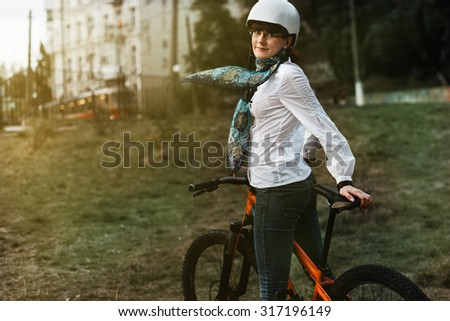 Portrait of happy young bicyclist riding in park on her bike - stock photo