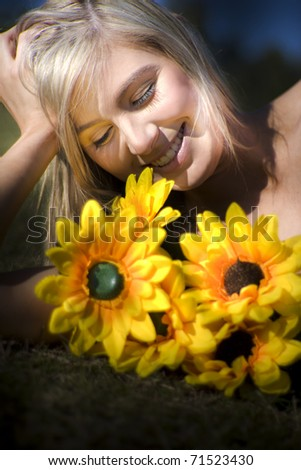 Portrait Of Happy Young Blond Haired Woman With Blooming Sunflowers Outdoors - stock photo
