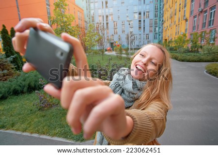 Portrait of happy young blonde smiling caucasian woman taking a selfie with mobile phone outdoors. - stock photo
