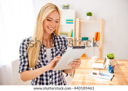 Portrait of happy young blonde using digital tablet in office - stock photo