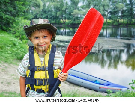 Portrait of happy young boy holding paddle near a kayak on the river, enjoying a lovely summer day - stock photo