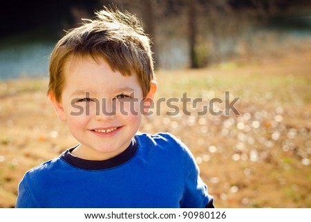 Portrait of happy young boy outdoors in image with copy space - stock photo