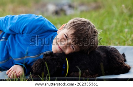 Portrait of happy young boy with his friendly pet - stock photo