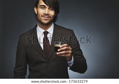Portrait of happy young business man offering you a cup of coffee against black background. Mixed race male model holding black coffee. - stock photo