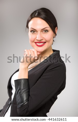 Portrait of happy young business woman at grey background - stock photo