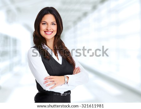 Portrait of happy young business woman over office background - stock photo