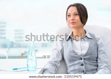 Portrait of happy young business woman thinking about something - stock photo