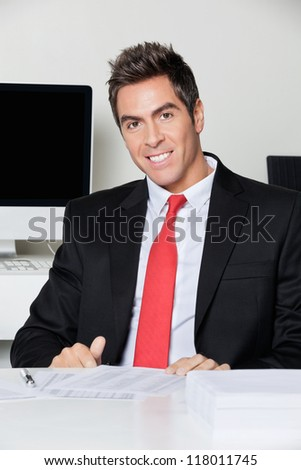 Portrait of happy young businessman sitting at desk in office - stock photo