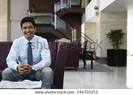 Portrait of happy young businessman sitting on sofa in hotel lobby - stock photo