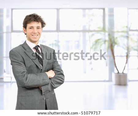 Portrait of happy young businessman standing in confident pose with arms crossed in office lobby, smiling. - stock photo