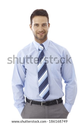 Portrait of happy young businessman standing with hand in pockets.