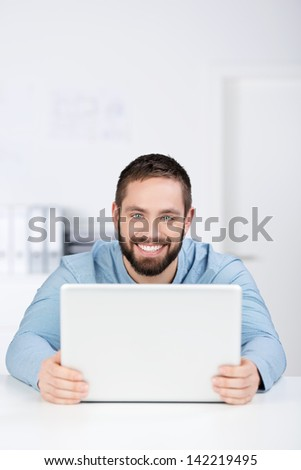 Portrait of happy young businessman with digital tablet at desk - stock photo