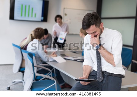 Portrait of happy young businessman with tablet computer office. People group on team meeting in background