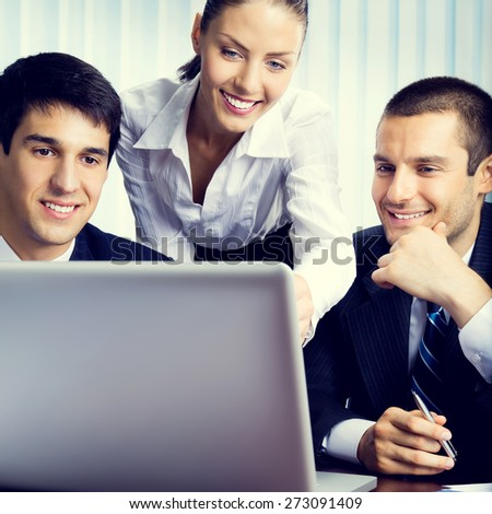 Portrait of happy young businesspeople working with laptop at office - stock photo