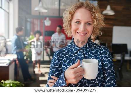 Portrait of happy young businesswoman holding a cup of coffee looking at camera and smiling. She is standing in her office with team of colleagues talking in background. - stock photo