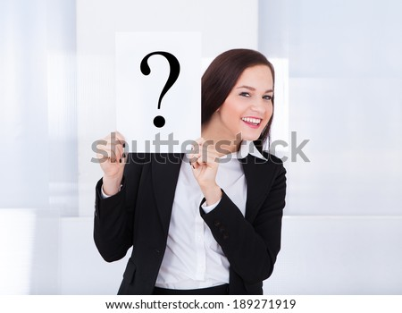 Portrait of happy young businesswoman holding question mark sign in office - stock photo