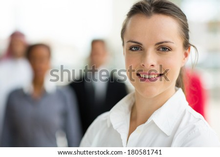 portrait of happy young businesswoman in front of colleagues - stock photo