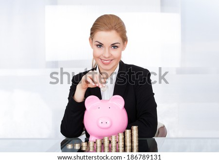Portrait Of Happy Young Businesswoman Inserting Coin In Piggybank - stock photo