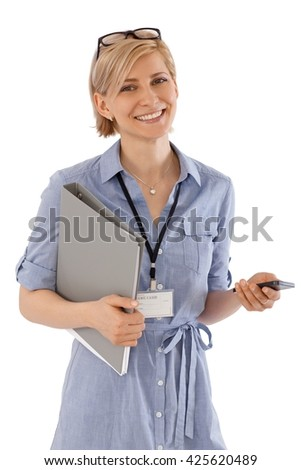 Portrait of happy young businesswoman smiling, holding folder with nametag hanging in neck. - stock photo