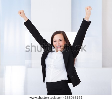 Portrait of happy young businesswoman standing in office