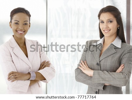 Portrait of happy young businesswomen standing on office corridor, looking at camera, smiling.? - stock photo