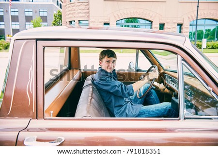 Portrait of happy young Caucasian teenage boy driving car, looking at camera and smiling