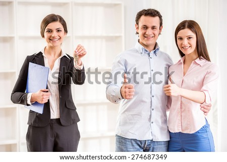 Portrait of happy young couple are showing thumb up and female realtor with keys in a new flat.