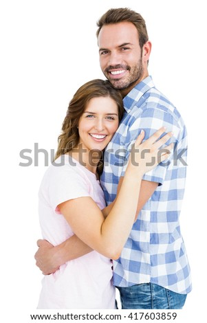 Portrait of happy young couple cuddling each other on white background