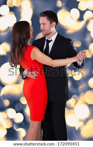 Portrait Of Happy Young Couple Dancing On Bokeh Background - stock photo