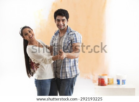Portrait of happy young couple dancing together at their new home - stock photo