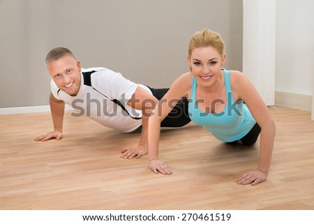 Portrait Of Happy Young Couple Doing Pushups