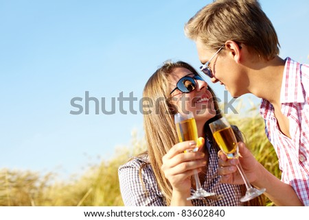 Portrait of happy young couple drinking wine outside - stock photo