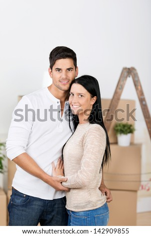 Portrait of happy young couple embracing against cardboard boxes in new house - stock photo
