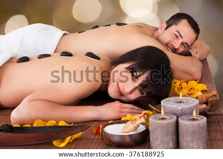 Portrait of happy young couple enjoying hot stone therapy in beauty spa