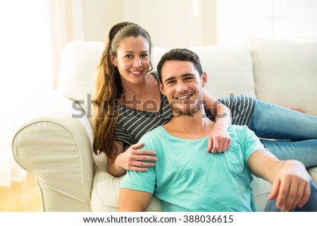 Portrait of happy young couple enjoying together in living room at home - stock photo